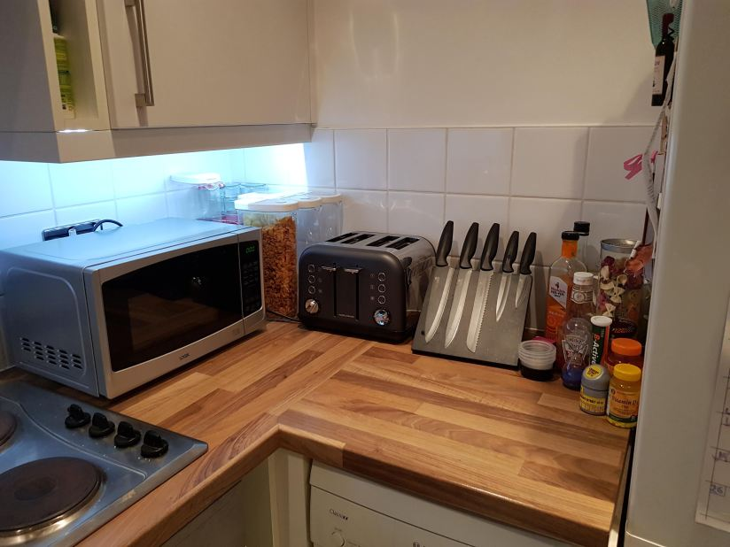 A small kitchen with wooden counter tops, a microwave, knife block, and toaster