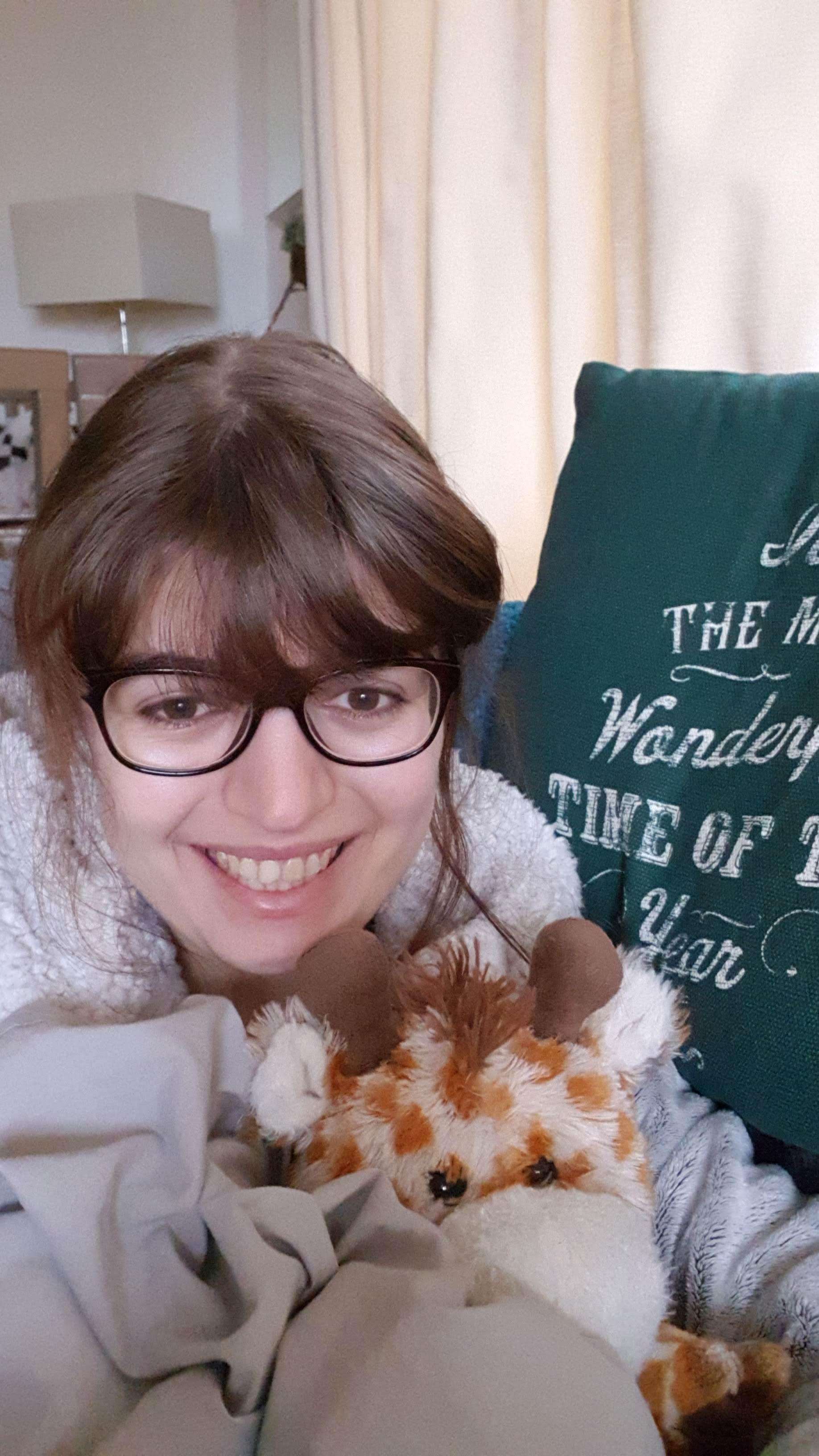 Jenny sitting on the sofa, covered by a big duvet and wearing a cosy dressing gown. There is a Christmas cushion in the background that says 'the most wonderful time of the year' and she's cuddling a giraffe teddy and smiling.